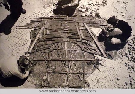Calceteiros pavimentando passeio com o molde de uma caravela, c. 1950. Lisboa, Portugal.
