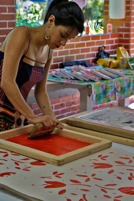 Ana Carolina compenetrada na impressão do seu estêncil floral